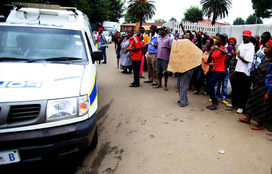 Residents shout at a passing police vehicle outside a Daveyton police station as they protest the death of taxi driver Mido Macia, who had been accused of parking in the wrong spot. Photo: Associated Press
