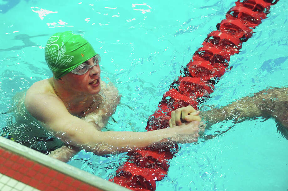 Newtown's Jacob Branchflower congratulates another swimmer after winning the fifth of six mixed 100-yard butterfly heats at the SWC boys swimming championship at Masuk High School in Monroe, Conn. Friday, March 1, 2013. Photo: Tyler Sizemore / The News-Times
