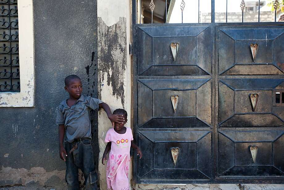 Two young children stand outside a house marked with black `Xs´ in the Bamburi area of the coastal city of Mombasa, on March 1, 2013. Locals dont know who is behind the attack but suspect a tribalist act to incite fear within the non-coastal tribes as election day nears. It was used in Kenya´s last elections to demarcate people who are not traditionally from respective areas. Photo: Ivan Lieman, AFP/Getty Images