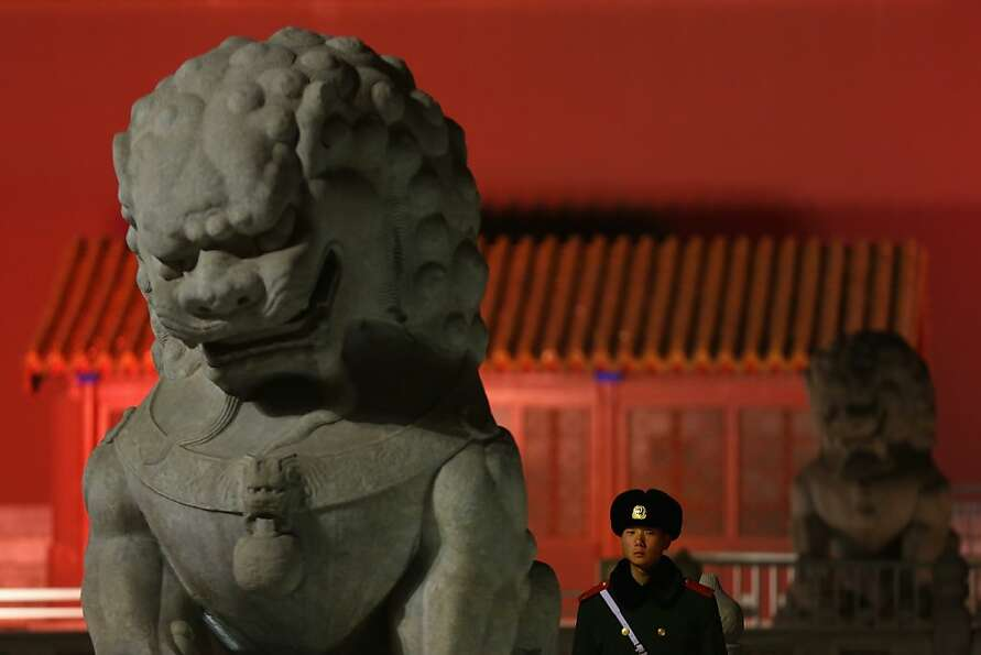 A Chinese policeman guards between two stone lions in front of the Tiananmen Gate on March 1, 2013 i