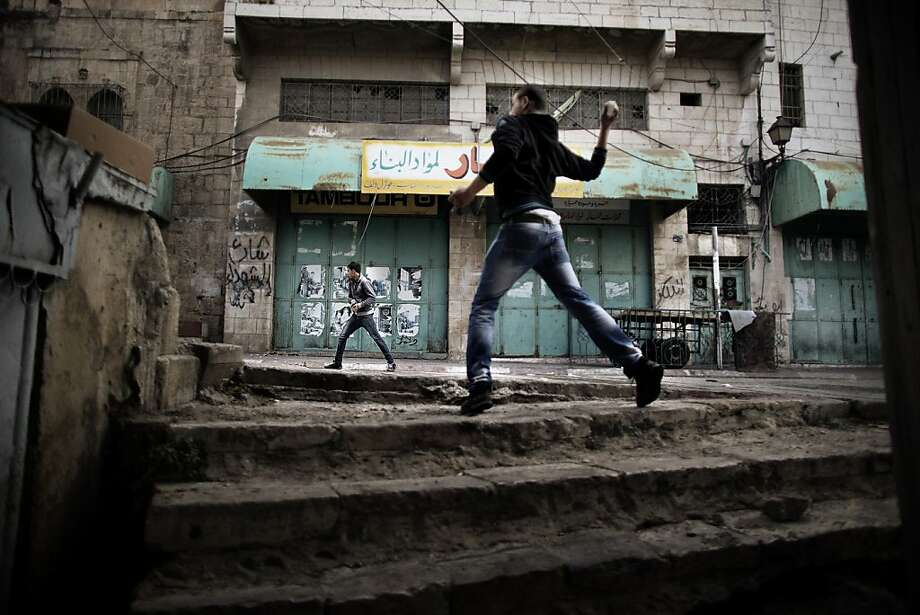 Palestinian protesters throw stones towards Israeli troops during clashes in the old city of Hebron on March 1, 2013 following a protest demanding the reopening of Shuhada Street, the one-time heart of the city. Flanked by a handful of Jewish settlement enclaves, the Shuhada Street was partially closed off in 1994 after local settler Baruch Goldstein opened fire on Muslim worshippers at the city's Al-Ibrahimi mosque, killing 29 of them. Photo: Marco Longari, AFP/Getty Images