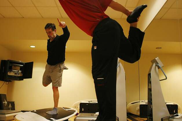 Working out atop a simulated surfboard helps build muscle. Photo: James Tensuan, The Chronicle