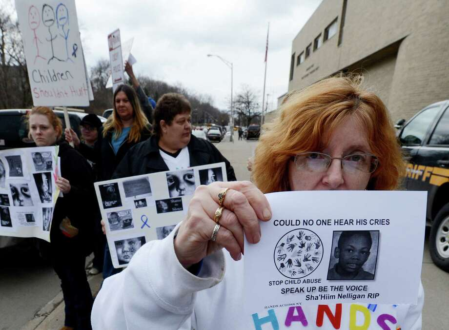 Laurie Russell holds a photo of a youngster that was alleged to have been murdered by his grandmother as other members of Hands Across NewYork march for greater awareness of child abuse March 1, 2013, in front of the Schenectady County Jail in Schenectady N.Y.   (Skip Dickstein/Times Union) Photo: SKIP DICKSTEIN / 10021379A