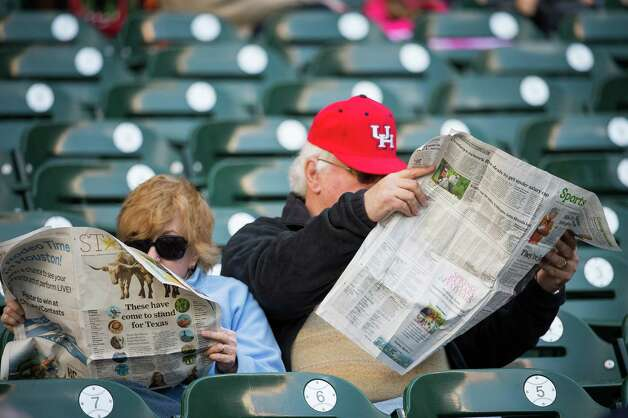 Fans read the newspaper during a break in the action during the Astros Foundation College Classic at Minute Maid Park, Friday, March 1, 2013, in Houston. Photo: Smiley N. Pool, Houston Chronicle / © 2013  Houston Chronicle
