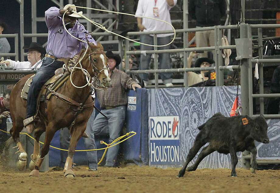 Fred Whitfield on his way to a score of 9.5 seconds in the tie-down roping competition at RodeoHouston in Reliant Stadium Friday, March 1, 2013, in Houston. Photo: James Nielsen, Houston Chronicle / © 2013  Houston Chronicle