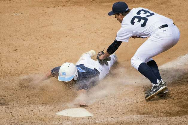 North Carolina outfielder Chaz Frank (2) touches the plate just ahead of the tag from Rice pitcher Zech Lemond (33) to score the winning run on a wild pitch in the ninth inning of a 2-1 victory during the Astros Foundation College Classic at Minute Maid Park, Friday, March 1, 2013, in Houston. Photo: Smiley N. Pool, Houston Chronicle / © 2013  Houston Chronicle