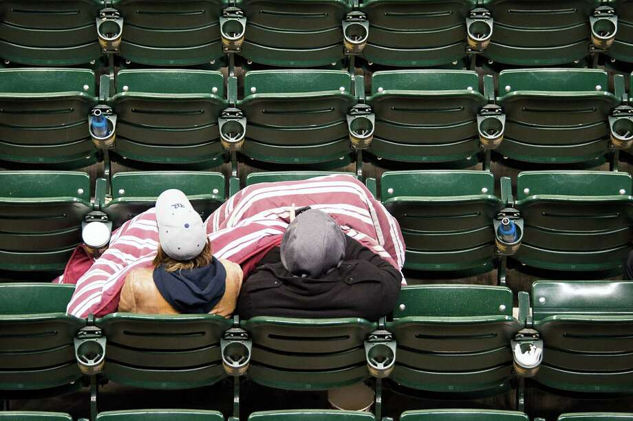 Fans huddle under a blanket as they watch Rice play North Carolina. Photo: Smiley N. Pool, Houston Chronicle / © 2013  Houston Chronicle