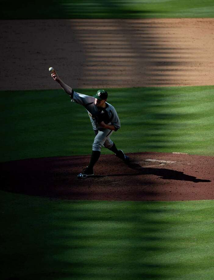 Shadows fall over the stadium as Baylor pitcher Miles Landry delivers a pitch during the ninth inning of a victory over California. Photo: Smiley N. Pool, Houston Chronicle / © 2013  Houston Chronicle