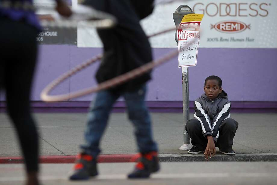A young boy watches people hula-hoop along Telegraph Avenue during the First Friday event after a shooting near last month's street festival killed one person and injured three others. Photo: Lacy Atkins, The Chronicle