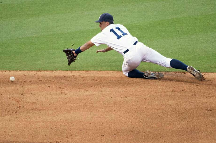 Rice shortstop Ford Stainback dives for a grounder off the bat of North Carolina's Michael Russell in the eighth inning. Photo: Smiley N. Pool, Houston Chronicle / © 2013  Houston Chronicle