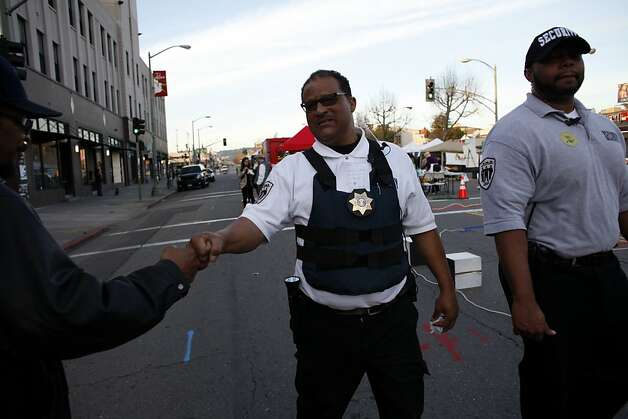 Security guard Chaney Timms, center, greets people as he patrols Telegraph Avenue duirng the First Friday event, Friday March 1, 2013, in Oakland, Calif. The mood is different said some spectators in the wake of shooting during last month's event leaving one person dead. Photo: Lacy Atkins, The Chronicle