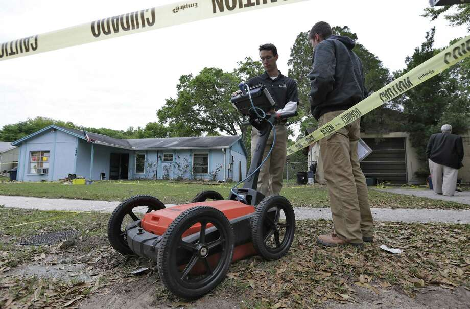 Engineers work in front of a home that appears OK from the outside but remains unstable after a sinkhole opened up underneath a bedroom and swallowed a man in Seffner, Fla. Photo: Chris O'Meara / Associated Press