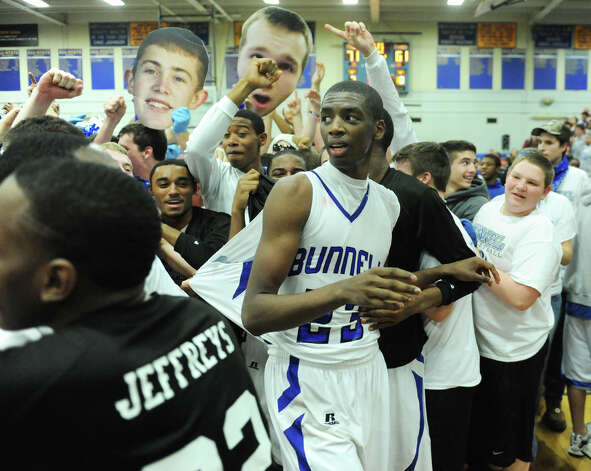 Bunnell players are mobbed as their home crowd rushes the court after their 71-61 win over Bethel in the SWC Boys Basketball Championship game at Bunnell High School in Stratford, Conn. Thursday, Feb. 28, 2013. Photo: Tyler Sizemore / The News-Times