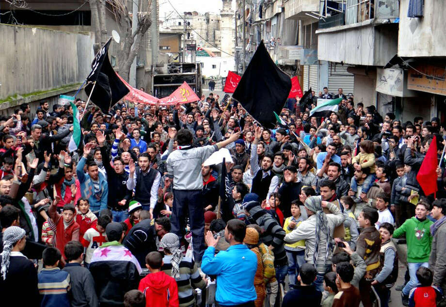 Anti-government protesters hold banners and chant slogans during a demonstration in  in Aleppo, Syria. Rebel leader Gen. Salim Idris is seeking weapons aid from other countries. Photo: Aleppo Media Center AMC / Associated Press
