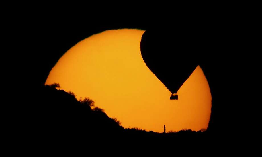 A hot air balloon decends to land as the sun sets north of Phoenix Friday, March 1, 2013. Photo: Charlie Riedel, Associated Press