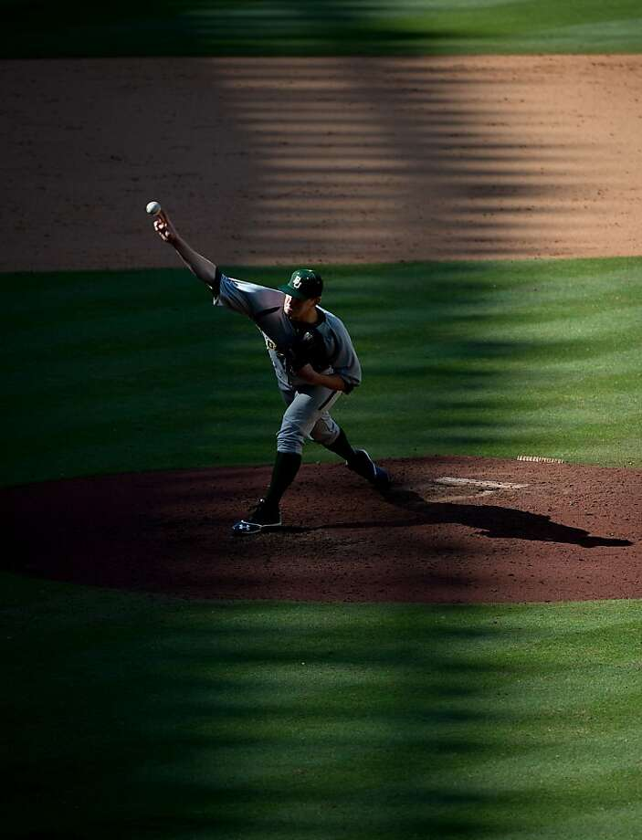 Shadows fall over the stadium as Baylor pitcher Miles Landry delivers a pitch during the ninth inning of a victory over California  in the Astros Foundation College Classic baseball game at Minute Maid Park, Friday, March 1, 2013, in Houston. Photo: Smiley N. Pool, Associated Press