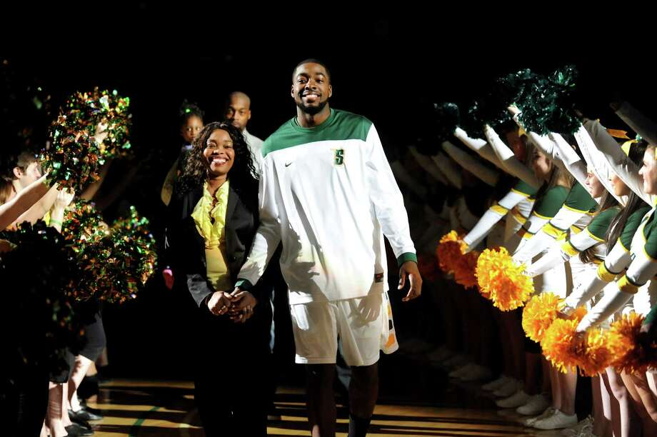 Siena's O.D. Anosike , center, walks with his mother, Ngozi, left, when he's honored on Senior Day before their basketball game against Marist on Friday, March 1, 2013, at Times Union Center in Albany, N.Y.  (Cindy Schultz / Times Union) Photo: Cindy Schultz / 10021367A