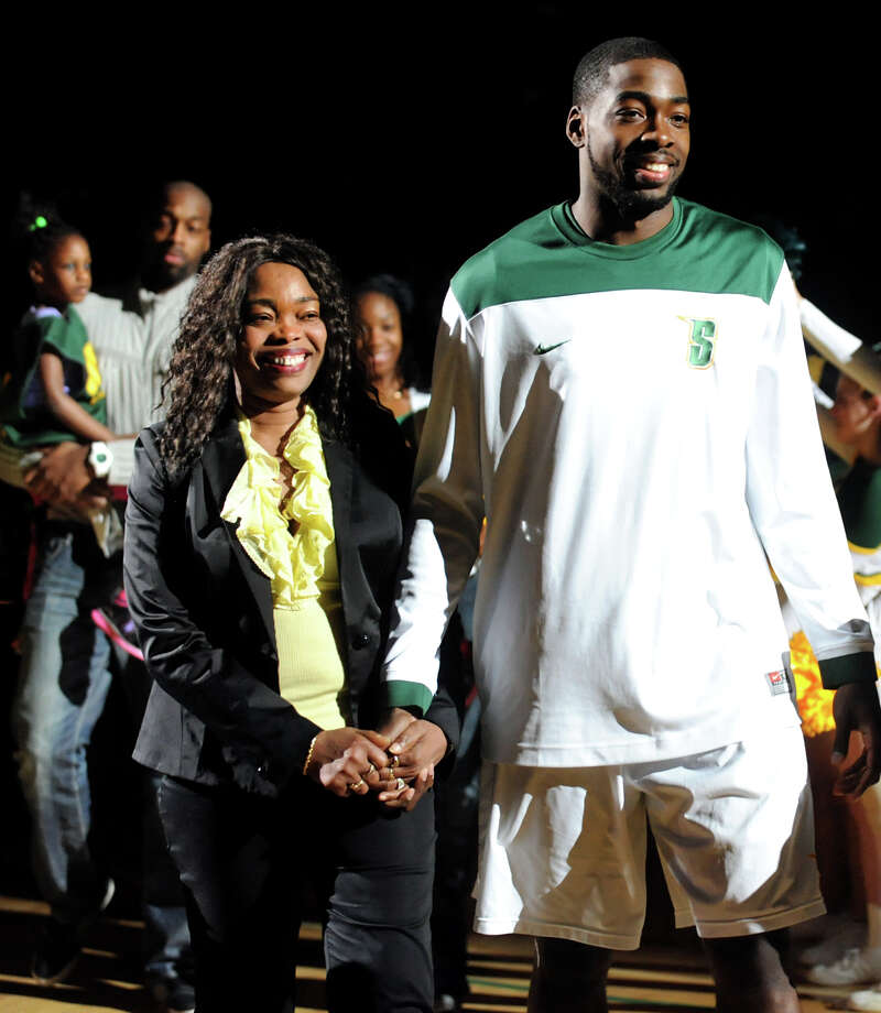 Siena's O.D. Anosike , right, walks with his mother, Ngozi, when he's honored on Senior Day before their basketball game against Marist on Friday, March 1, 2013, at Times Union Center in Albany, N.Y. (Cindy Schultz / Times Union) Photo: Cindy Schultz / 10021367A