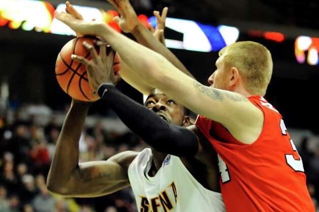 Siena's O.D. Anosike , center, works to get past Marist's Pieter Prinsloo (34) during their basketball game on Friday, March 1, 2013, at Times Union Center in Albany, N.Y. Marist wins 76-74. (Cindy Schultz / Times Union) Photo: Cindy Schultz / 10021367A