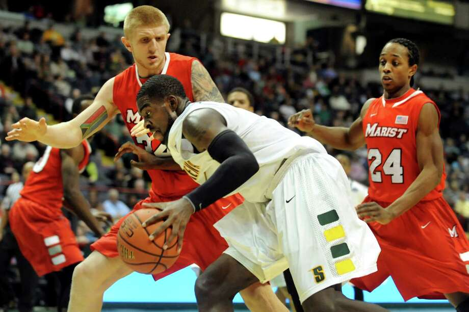 Siena's O.D. Anosike (1), center, drives past the defense of Marist's Pieter Prinsloo (34), left, and Manny Thomas (24) during their basketball game on Friday, March 1, 2013, at Times Union Center in Albany, N.Y. (Cindy Schultz / Times Union) Photo: Cindy Schultz / 10021367A
