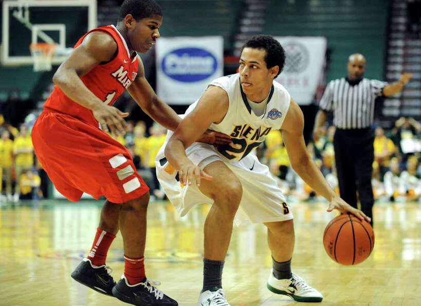 Siena's Chris Leppanen (20), right, holds Marist's Isaiah Morton (11) at bay during their basketball