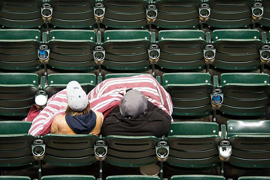Fans huddle under a blanket as they watch Rice play North Carolina  in the Astros Foundation College Classic baseball game at Minute Maid Park, Friday, March 1, 2013, in Houston. Photo: Smiley N. Pool, Associated Press