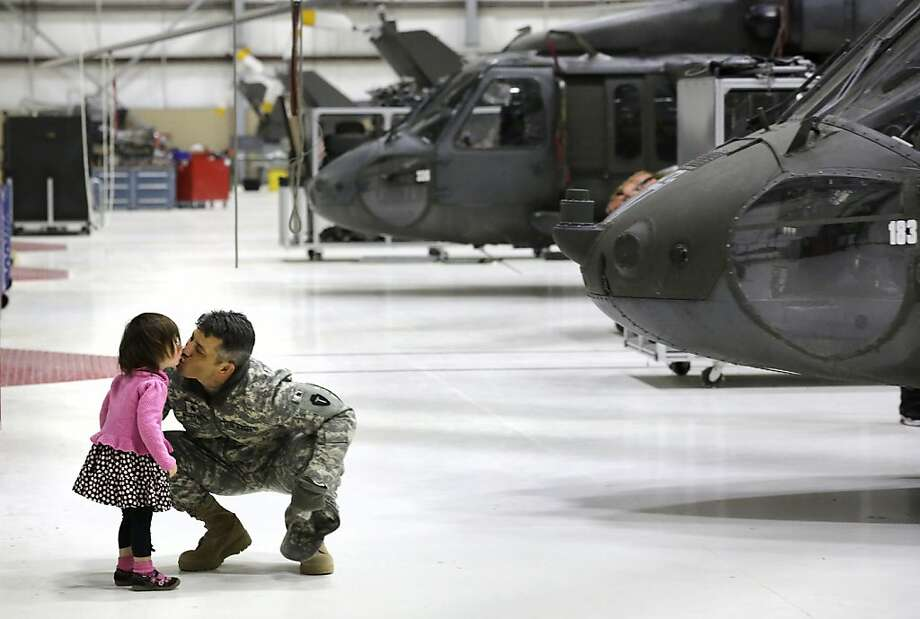 In this Wednesday, Feb. 27, 2013, file photo, Lt. Col. James Nugent of Austin, gets a kiss from his daughter, Sienna Nugent, as members of the 449th Aviation Support Battalion of the Army National Guard participate in a mobilization ceremony at the Army Aviation Support Facility in Austin, Texas in advance of their deployment to Kuwait. Photo: Bob Owen, Associated Press