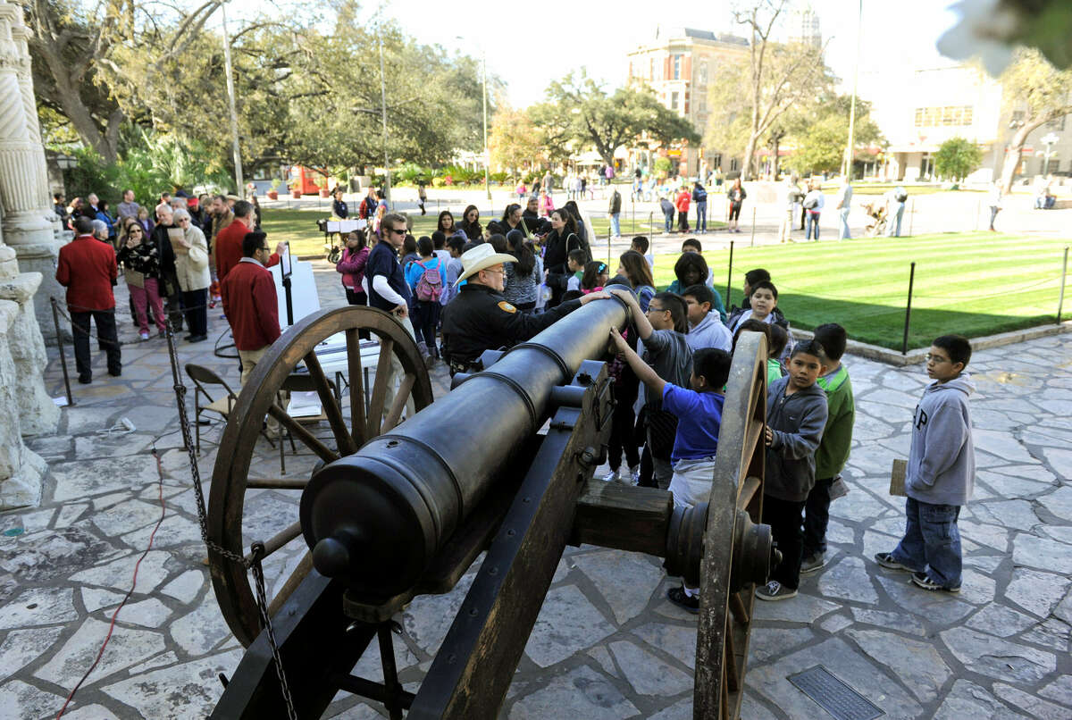 Children look over a replica of the 18-pound cannon fired in response to Gen. Antonio López de Santa Anna's demand for surrender of the Alamo.