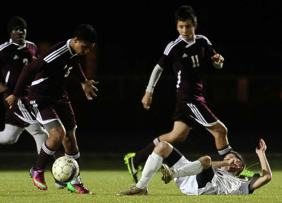 Central player Herman Sifuentes, #5, steals the ball from Nederlands Cor Binagia, #2, after he hits the ground in the second half of the Nederland High School boys soccer game against Central High School in Nederland on Friday, March, 1, 2013.  Nederland won over Central 2 - 0. Photo taken: Randy Edwards/The Enterprise