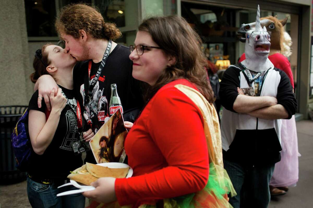 Alice Woods, left, kisses her boyfriend, Andrew Bowen, center left, while Fiona Bowen, center, waits in line as equine-headed attendees lurk nearby on the opening day of the annual Emerald City Comicon at the Washington State Convention Center in Seattle on Friday, March 1, 2013.