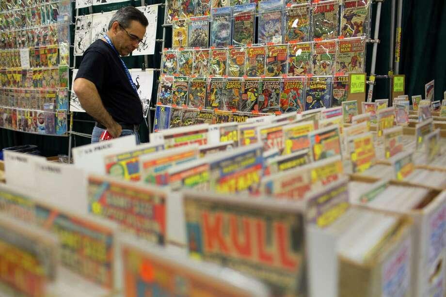 A comic dealer observes his collection of old-school comics. Photo: JORDAN STEAD / SEATTLEPI.COM