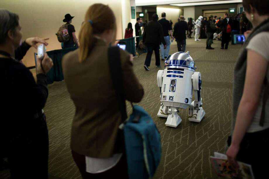 Girls take cell phone pictures of a lone, milling R2D2 robot. Photo: JORDAN STEAD / SEATTLEPI.COM