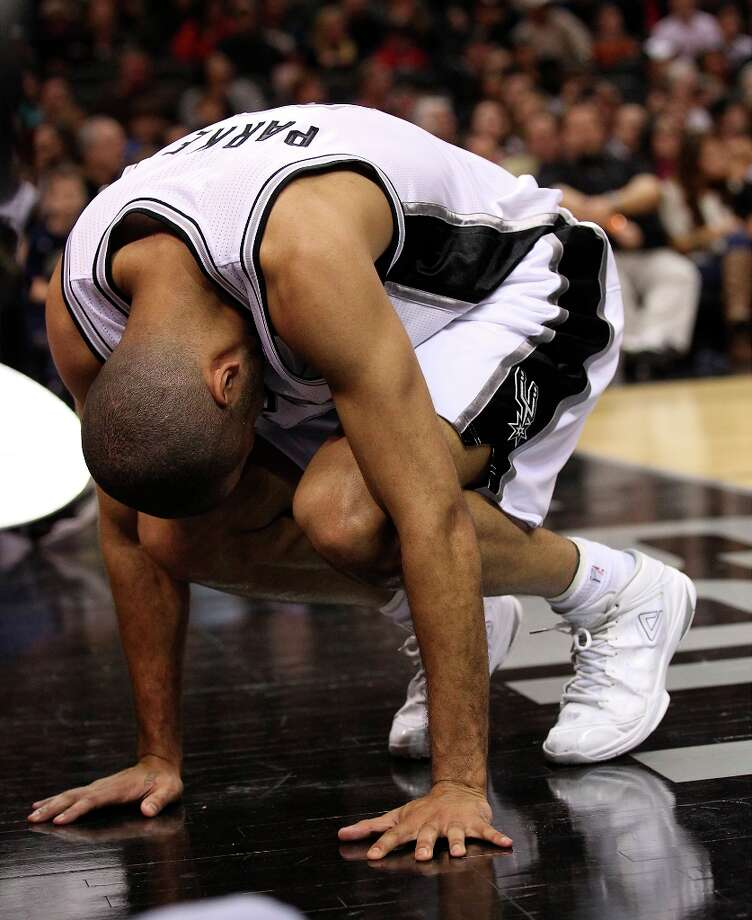 The Spurs' Tony Parker (9) is bent over in pain after a play against the Sacramento Kings late in the third quarter at the AT&T Center on Friday, Mar. 1, 2013. Parker left and was later reported having a left ankle sprain and did not return to the game. Spurs defeated the Kings, 130-102. Photo: Kin Man Hui, San Antonio Express-News / © 2012 San Antonio Express-News