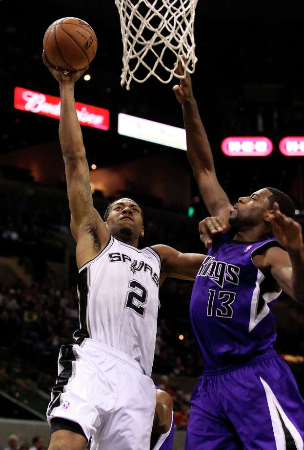 Spurs' Kawhi Leonard (02) goes the basket against Sacramento Kings' Tyreke Evans (13) in the second half at the AT&T Center on Friday, Mar. 1, 2013. Spurs defeated the Kings, 130-102. Photo: Kin Man Hui, San Antonio Express-News / © 2012 San Antonio Express-News