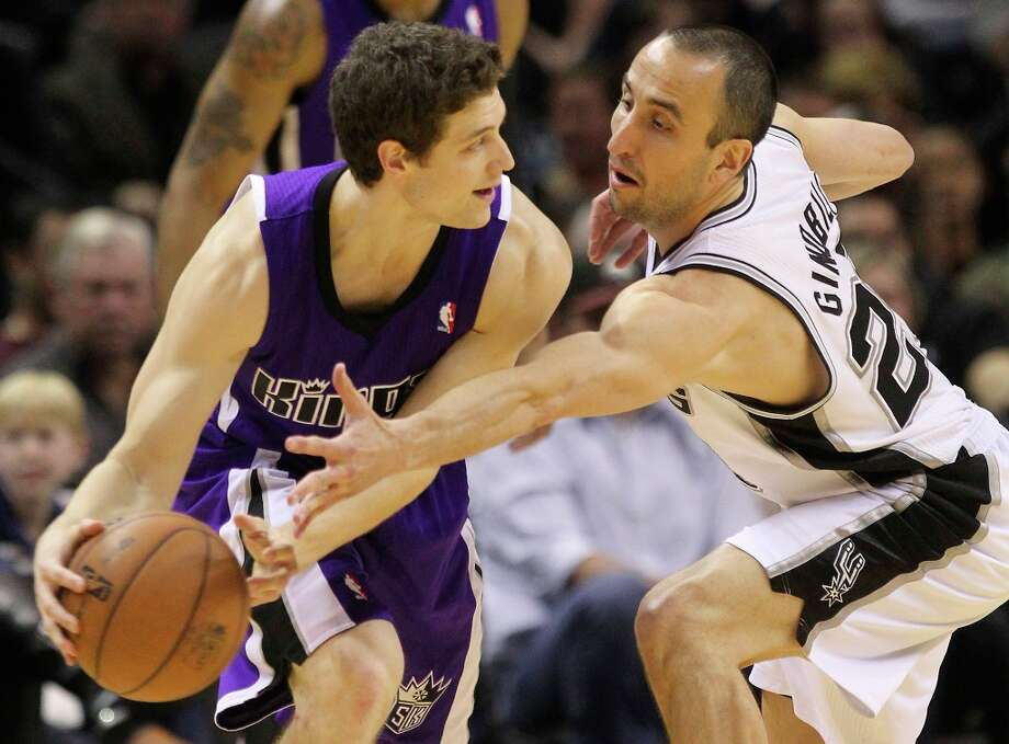 The Spurs' Manu Ginobili (20) reaches to attempt a steal against Sacramento Kings' Jimmer Fredette (07) in the second half at the AT&T Center on Friday, Mar. 1, 2013. Spurs defeated the Kings, 130-102. Photo: Kin Man Hui, San Antonio Express-News / © 2012 San Antonio Express-News