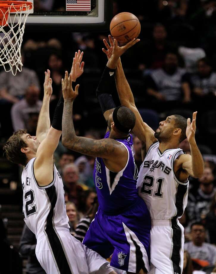 The Spurs' Tiago Splitter (22) and Tim Duncan (21) defends against Sacramento Kings' DeMarcus Cousins (15) in the first half at the AT&T Center on Friday, Mar. 1, 2013. Photo: Kin Man Hui, San Antonio Express-News / © 2012 San Antonio Express-News