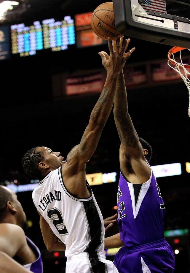 The Spurs' Kawhi Leonard (2) goes the basket against Sacramento Kings' James Johnson (52) in the first half at the AT&T Center on Friday, Mar. 1, 2013. Photo: Kin Man Hui, San Antonio Express-News / © 2012 San Antonio Express-News