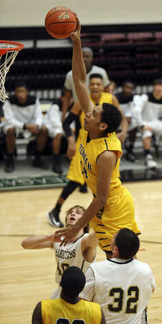 Brennan's Jordan Murphy goes up for a dunk between Port Lavaca Calhoun's Taylor Lee (left) and Isaac Cardona during the first half. Brennan won 63-42 and will face Alamo Heights at 2 p.m. today at Littleton Gym for a berth in the 4A state tourney. Photo: Edward A. Ornelas / San Antonio Express-News