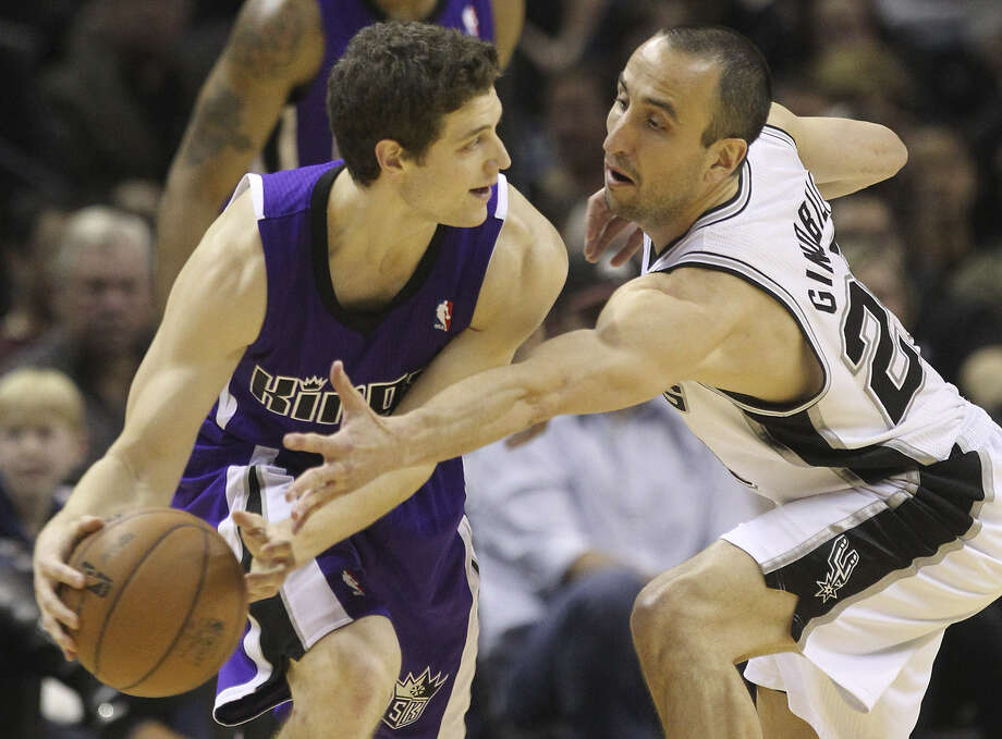 The Spurs' Manu Ginobili (right), trying to steal the ball from Sacramento's Jimmer Fredette, dished out a career-high 15 assists in Friday's blowout win. Photo: Kin Man Hui / San Antonio Express-News
