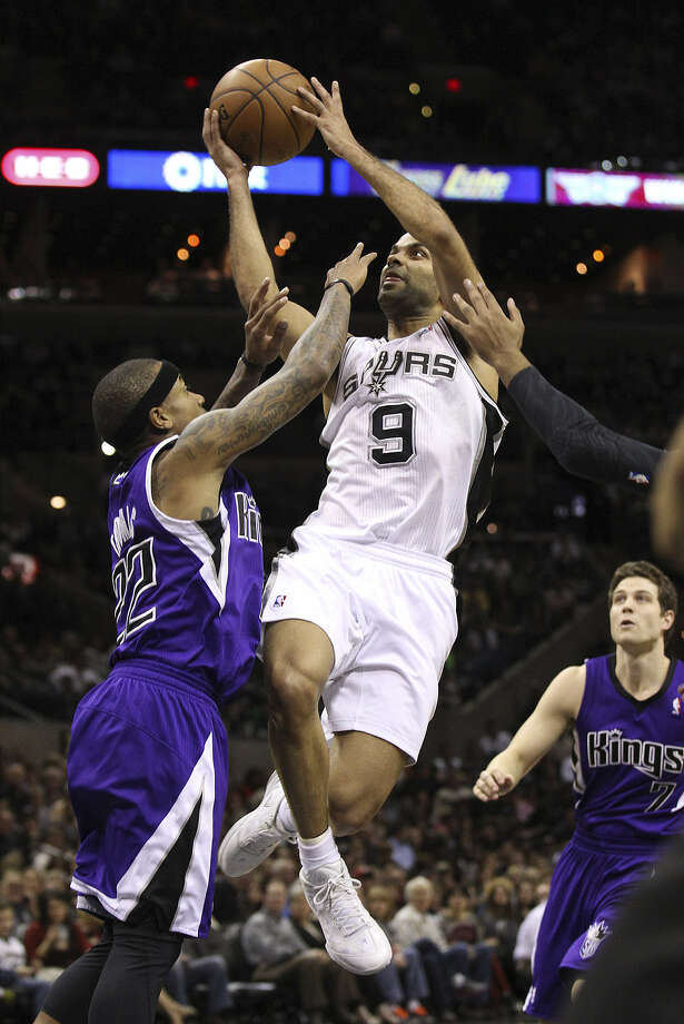 The Spurs' Tony Parker (middle) goes up for a shot against the Kings' Isaiah Thomas late in Friday's third quarter. Parker sprained his left ankle on the play and didn't return. Photo: Kin Man Hui / San Antonio Express-News