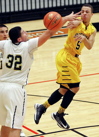 Brennan's John Azzinaro passes around Port Lavaca Calhoun's Isaac Cardona during second half action of their Region IV-4A semifinal game Friday March 1, 2013 at Littleton Gym. Brennan won 63-42. Photo: Edward A. Ornelas, Edward A. Ornelas / San Antonio Express-News / © 2013 San Antonio Express-News