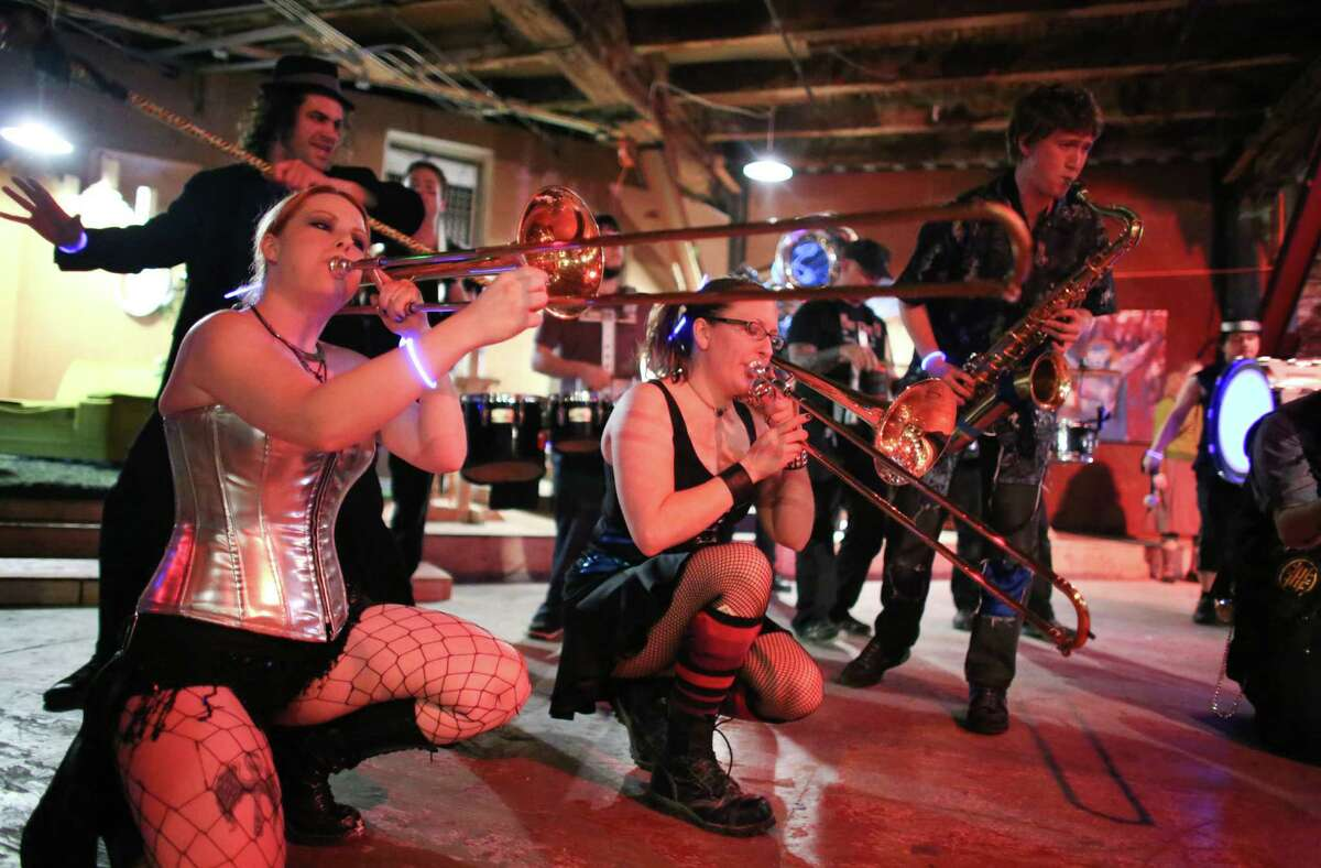 Members of the Chaotic Noise Marching Corps, including Emily Diehl, left, and Jeanette DuBois, center, perform during the kickoff night of Smash Putt on Friday, March 1, 2013 in Seattle's Sodo neighborhood. Smash Putt is like mini-golf with the added challenges of negotiating laser beams, power tools and other mechanical obstacles. Plus, you can play it while downing a beer.