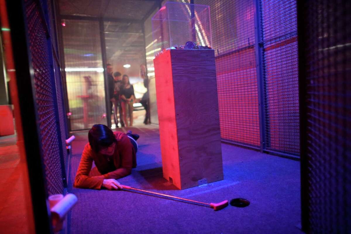Cecelia Gunn tries to avoid a laser beam sensor while sinking a ball in a hole during the kickoff night of Smash Putt on Friday, March 1, 2013 in Seattle's Sodo neighborhood. Smash Putt is like mini-golf with the added challenges of negotiating laser beams, power tools and other mechanical obstacles. Plus, you can play it while downing a beer.