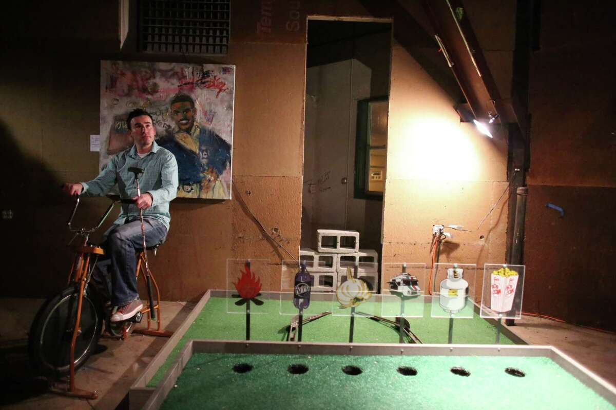 A participant rides a stationary bike during the kickoff night of Smash Putt on Friday, March 1, 2013 in Seattle's Sodo neighborhood. Smash Putt is like mini-golf with the added challenges of negotiating laser beams, power tools and other mechanical obstacles. Plus, you can play it while downing a beer.