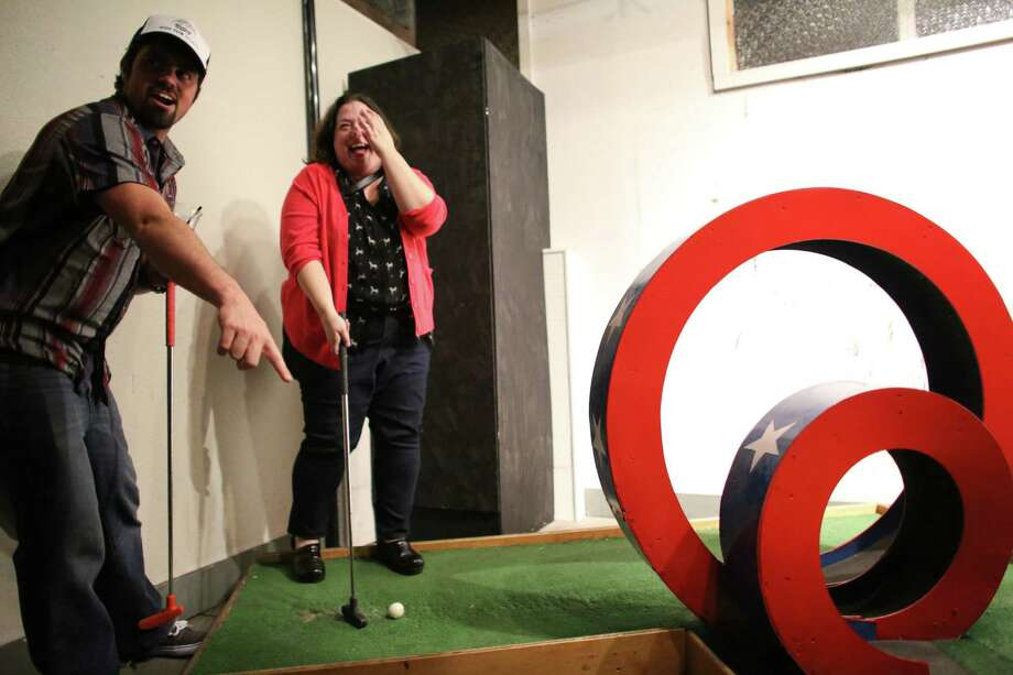 Lucas Shuler and Karla Hagemier try to figure out an obstacle during the kickoff night of Smash Putt on Friday, March 1, 2013 in Seattle's Sodo neighborhood. Smash Putt is like mini-golf with the added challenges of negotiating laser beams, power tools and other mechanical obstacles. Plus, you can play it while downing a beer. Photo: JOSHUA TRUJILLO / SEATTLEPI.COM