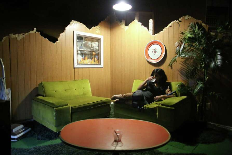 A participant rests in 'the living room,' one of the holes, during the kickoff night of Smash Putt o