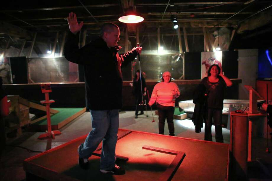 A participant sinks a ball during the kickoff night of Smash Putt on Friday, March 1, 2013 in Seattle's Sodo neighborhood. Smash Putt is like mini-golf with the added challenges of negotiating laser beams, power tools and other mechanical obstacles. Plus, you can play it while downing a beer. Photo: JOSHUA TRUJILLO / SEATTLEPI.COM