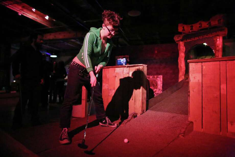 Shelly Delaney prepares to sink a ball during the kickoff night of Smash Putt on Friday, March 1, 2013 in Seattle's Sodo neighborhood. Smash Putt is like mini-golf with the added challenges of negotiating laser beams, power tools and other mechanical obstacles. Plus, you can play it while downing a beer. Photo: JOSHUA TRUJILLO / SEATTLEPI.COM