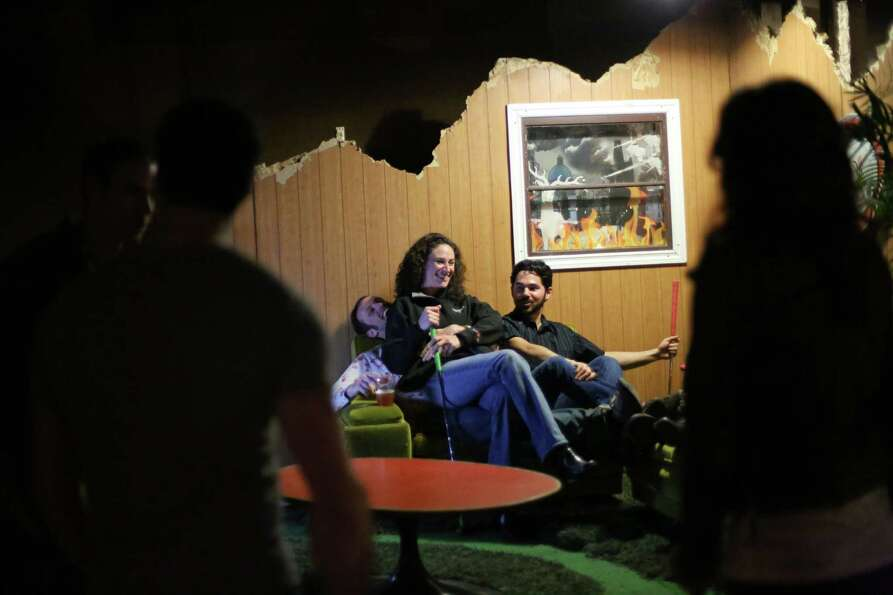 Participants rest in 'the living room,' one of the holes, during the kickoff night of Smash Putt on