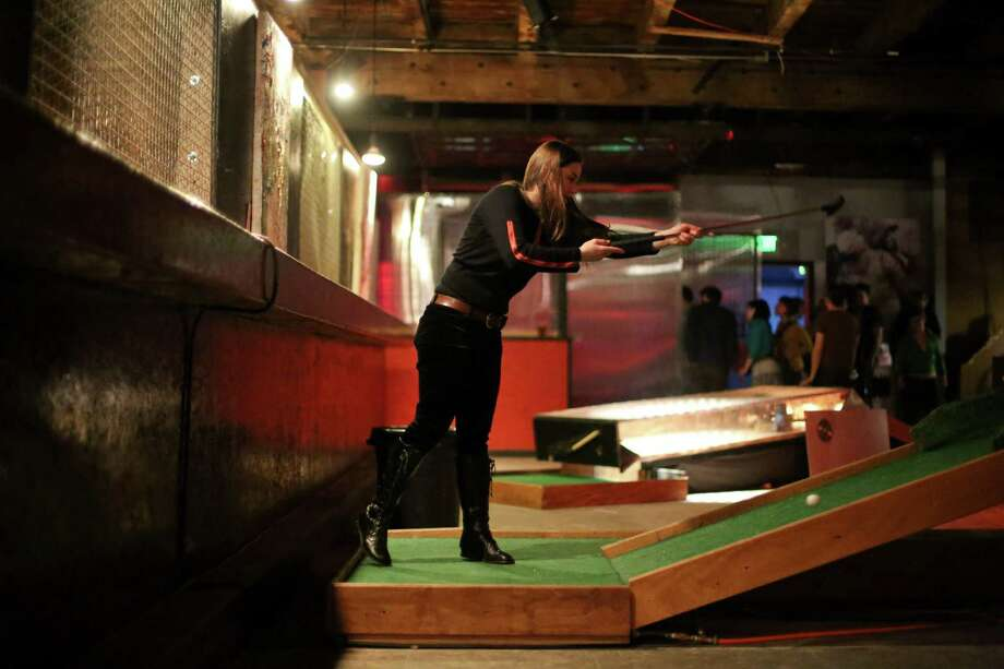 Jaewiga Pamula works to sink a ball during the kickoff night of Smash Putt on Friday, March 1, 2013 in Seattle's Sodo neighborhood. Smash Putt is like mini-golf with the added challenges of negotiating laser beams, power tools and other mechanical obstacles. Plus, you can play it while downing a beer. Photo: JOSHUA TRUJILLO / SEATTLEPI.COM